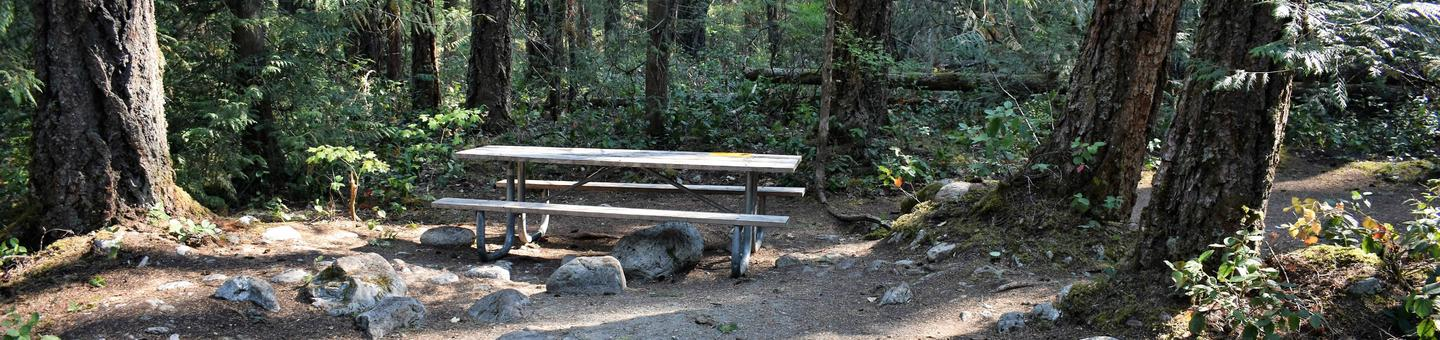 Picnic table surrounded by boulders and treesView of campsite