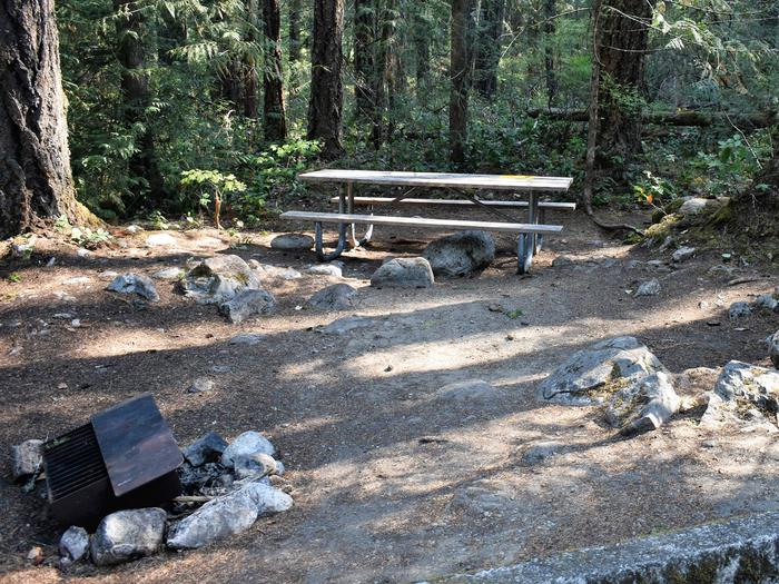 Picnic table and fire ring surrounded by boulders and treesView of campsite
