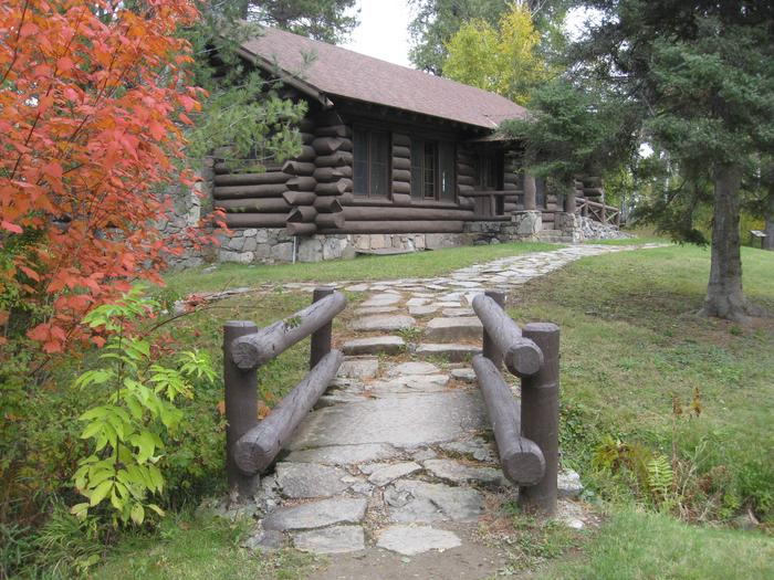 Picture of rock-lined path and log building.Access trail to log pavilion.  Pavilion is available for rent via recreation.gov.  Facilities include indoor tables, benches, and electricity.  Outdoor facilities include grill, picnic tables, open grassy area, parking, and outhouse.
