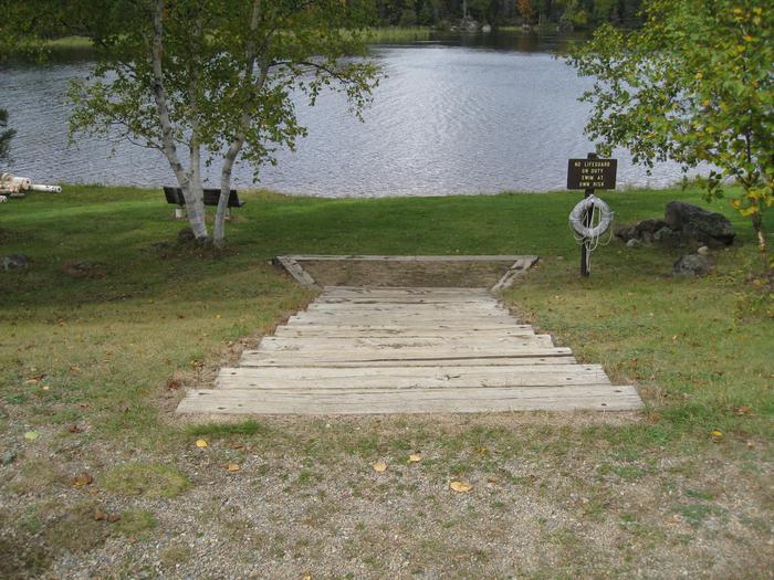 Picture of steps leading to lake.Beach area.  Steps provide access to sand beach area and benches.