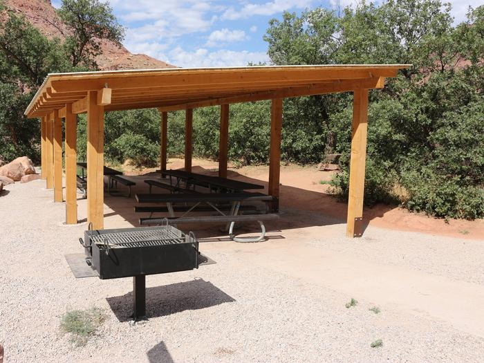 Close up of the Big Bend Group Site A shade shelter, picnic tables, and standing grill.