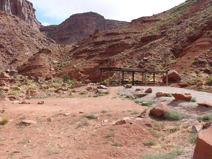 Big Bend Group Site C shade shelter and tent area. Red rock cliffs line the horizon.