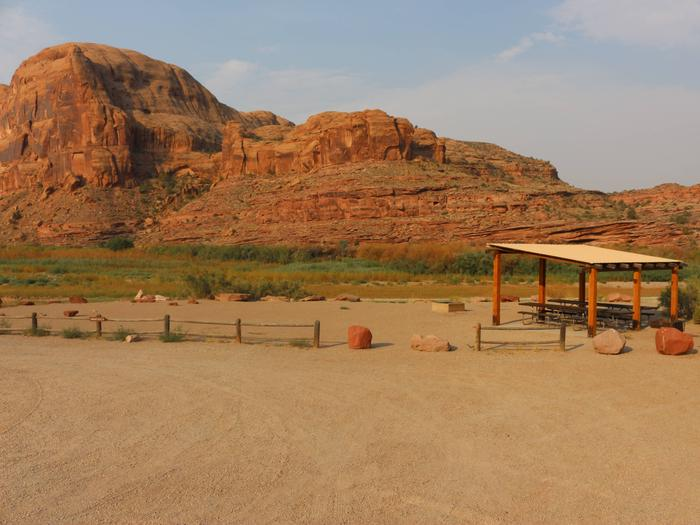 Shade shelters, picnic tables, parking area, and tent area at Gold Bar Group Site A. In the near distance is the Colorado River and rounded, red rock cliffs.