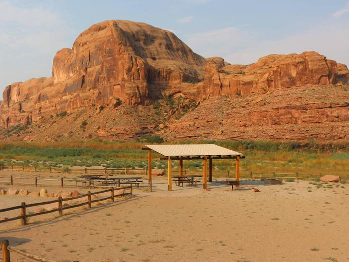 Gold Bar Group Site B shade shelter, picnic tables, and parking and tent area near the Colorado River with tall red rock cliffs in the distance.