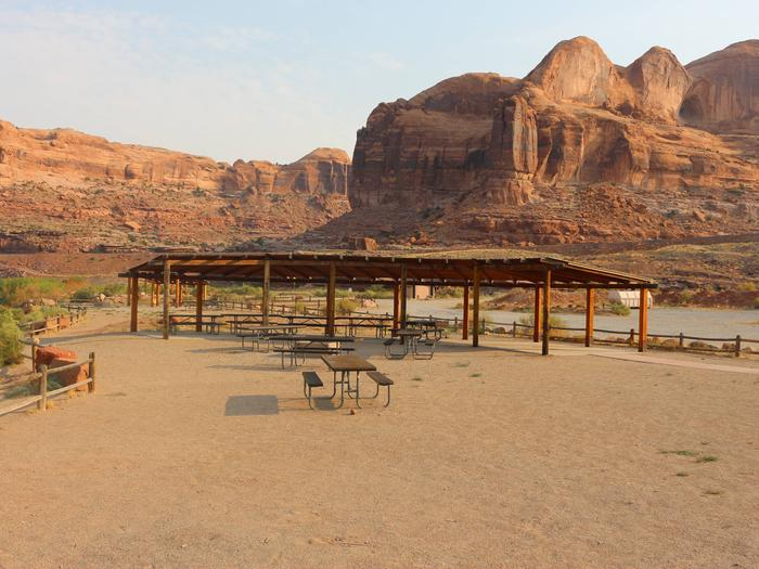 Gold Bar Group Site C large shade shelter and picnic tables with the Colorado River flowing nearby and tall, red rock cliffs in the distance.