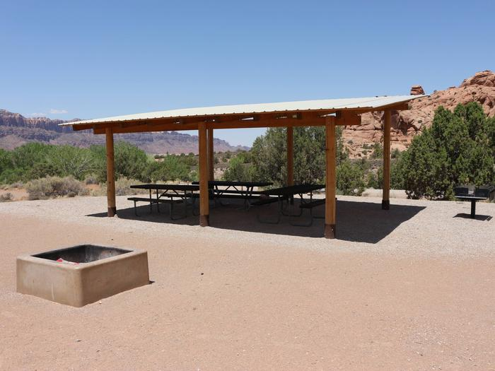 Ken's Lake Group Site B shade shelter, picnic tables, standing grill, and fire pit.