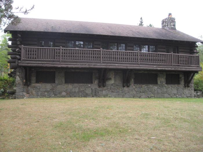 Picture of log building.Back of Pavilion, showing open grassy area.