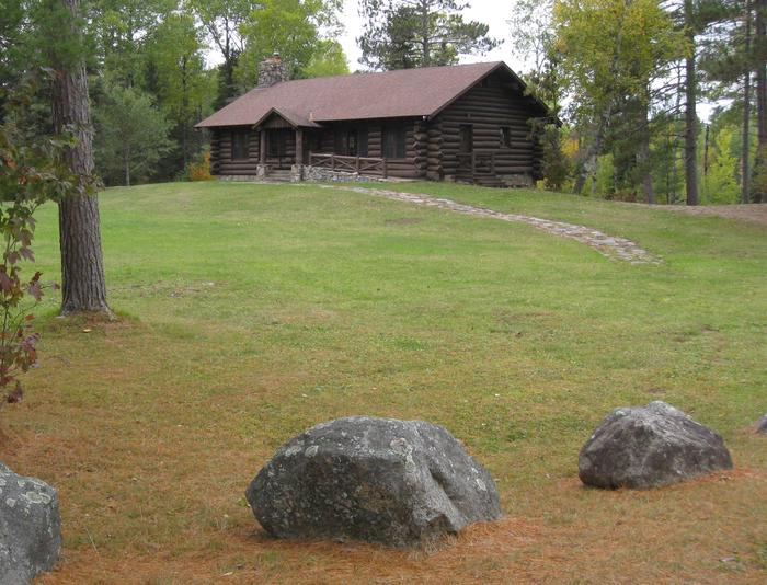 Picture of log building.Front of Kawishiwi Pavilion, showing open grassy area and access from small parking area. Adjacent to outdoor grill and picnic tables.