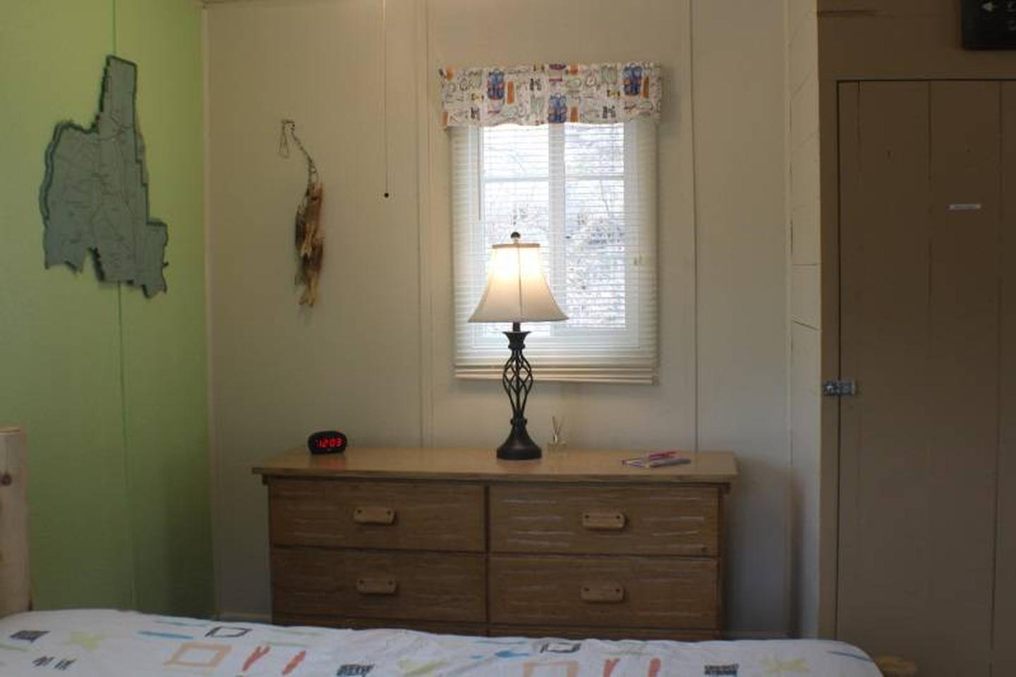 Dresser with lampCabin 1: View to right of full bed. Dresser with lamp, alarm clock with USB charging port.