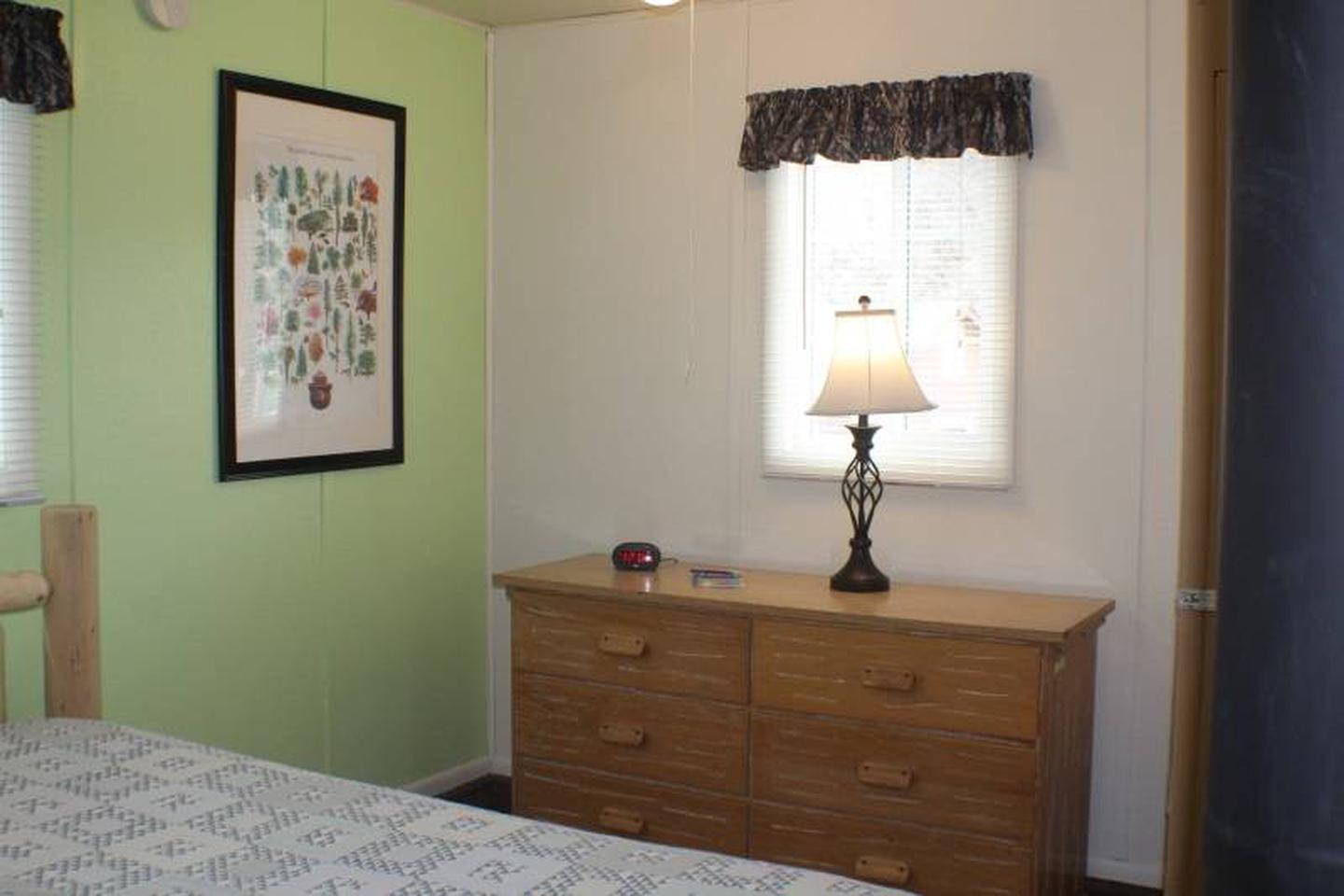 Dresser, lampCabin 2: View to right of full bed. Dresser with lamp, alarm clock with USB charging port.