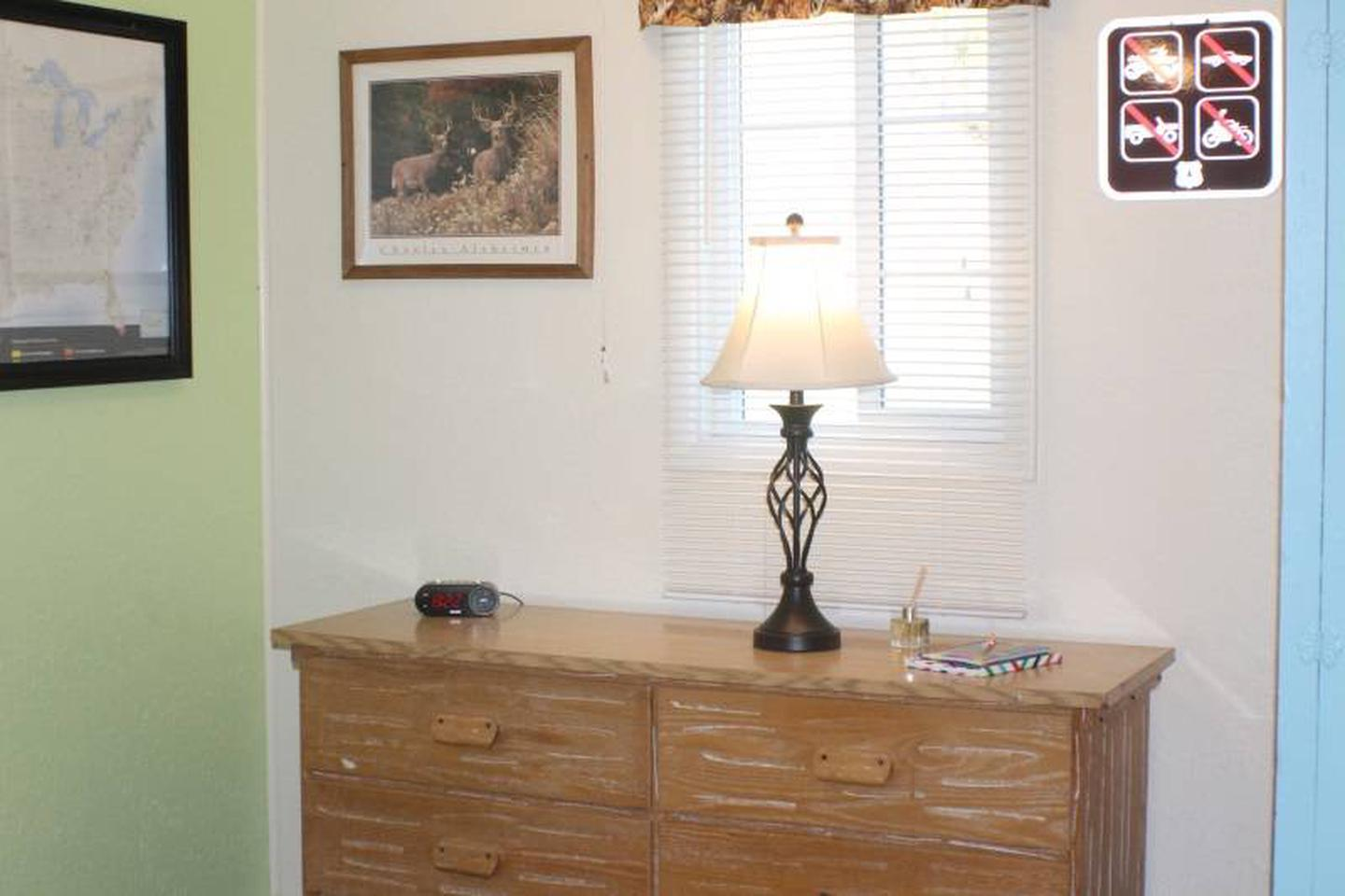 dresser with lampCabin 3: View to right of full bed. Dresser with lamp and alarm clock with USB charging port.
