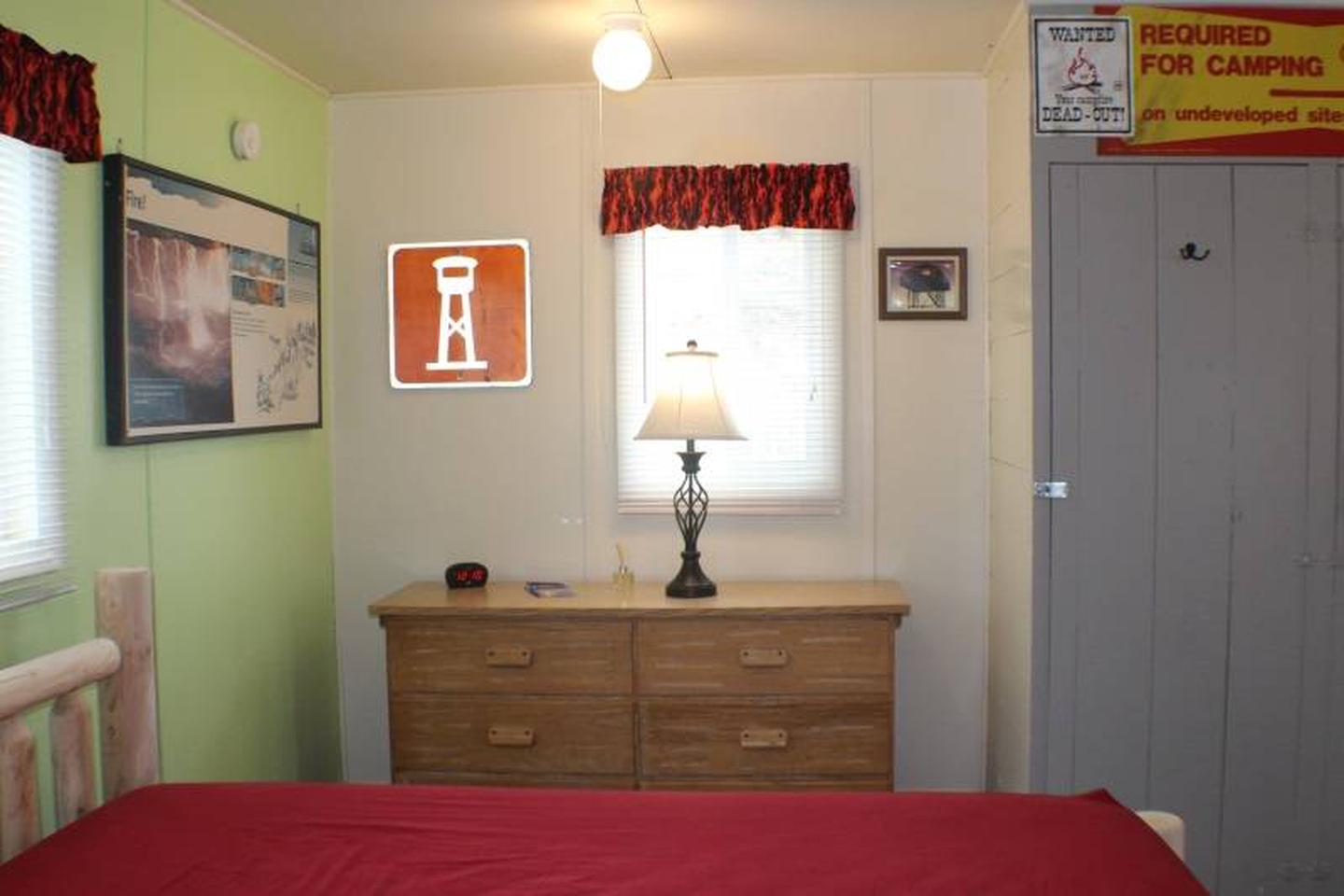 dresser, lampCabin 4: View to right of full bed. Dresser with lamp and alarm clock with USB charging port.