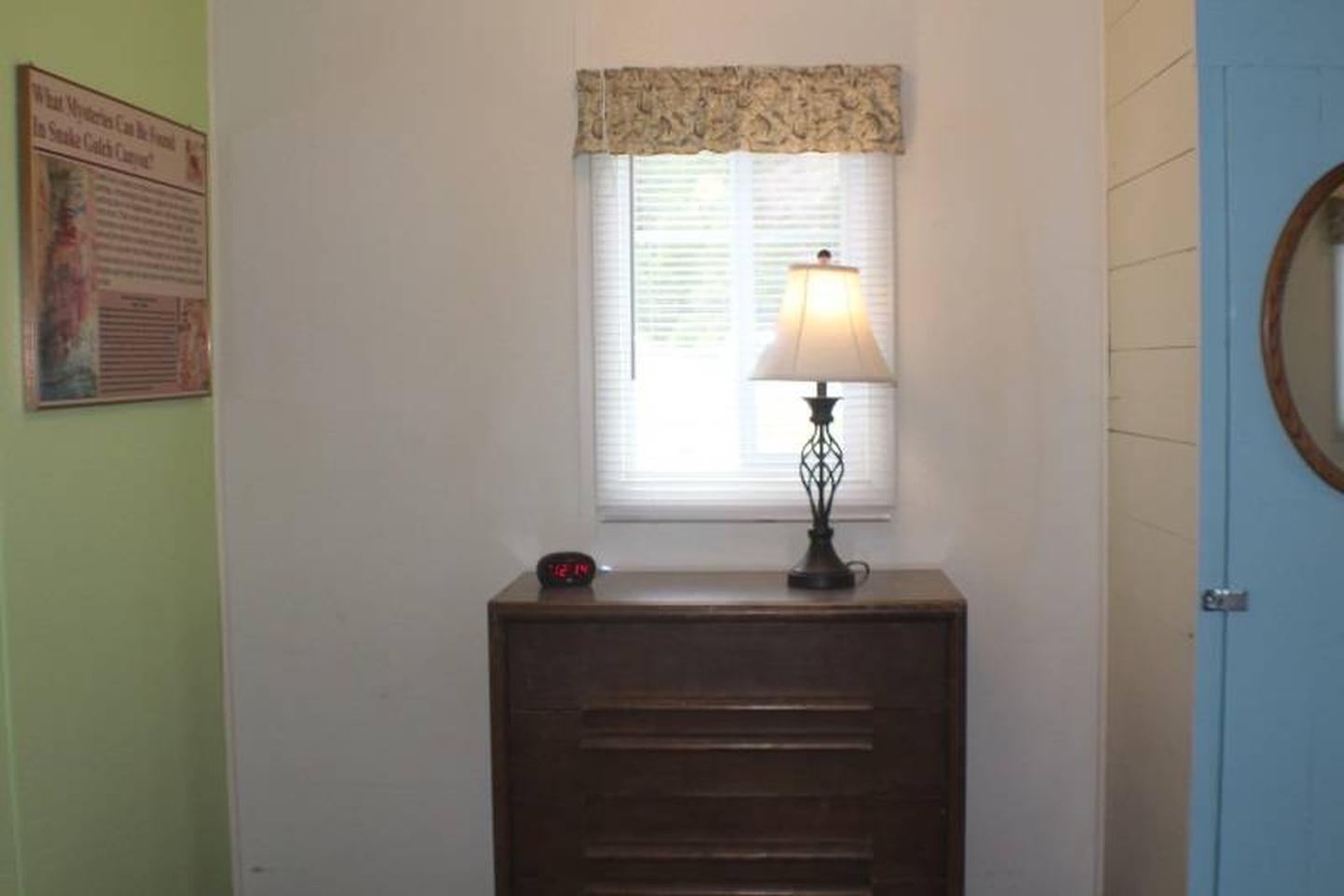 dresser, lampCabin 5: View to right of full bed. Dresser with lamp and alarm clock with USB charging port.