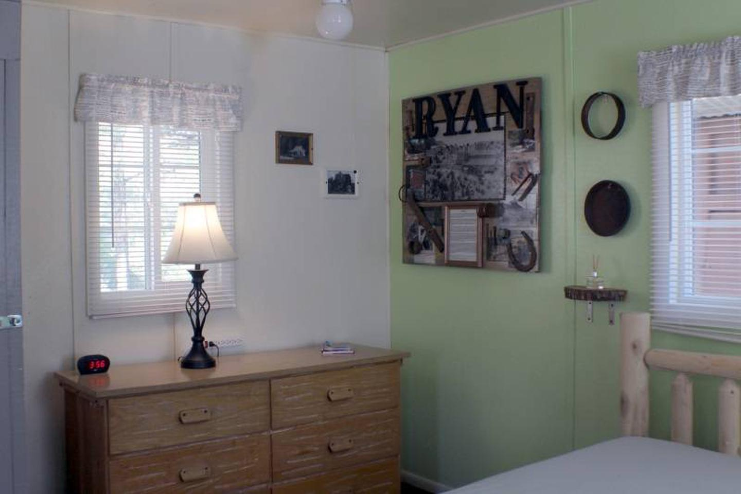 dresser, lampCabin 6: View to left of full bed. Dresser with lamp and alarm clock with USB charging port.