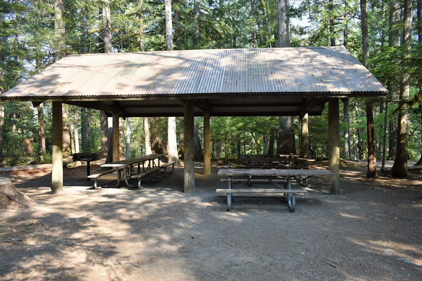 Large shelter which provides rain and sun protection to several picnic tables under shelterView of group shelter A