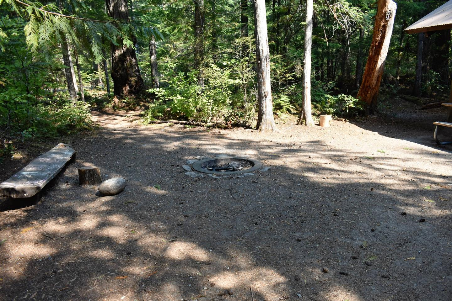Large, in-ground fire circle with bench nearbyView of fire circle