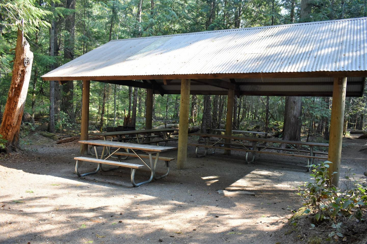 Group shelter which provides rain and sun protection to several picnic tables underneathView of group shelter B