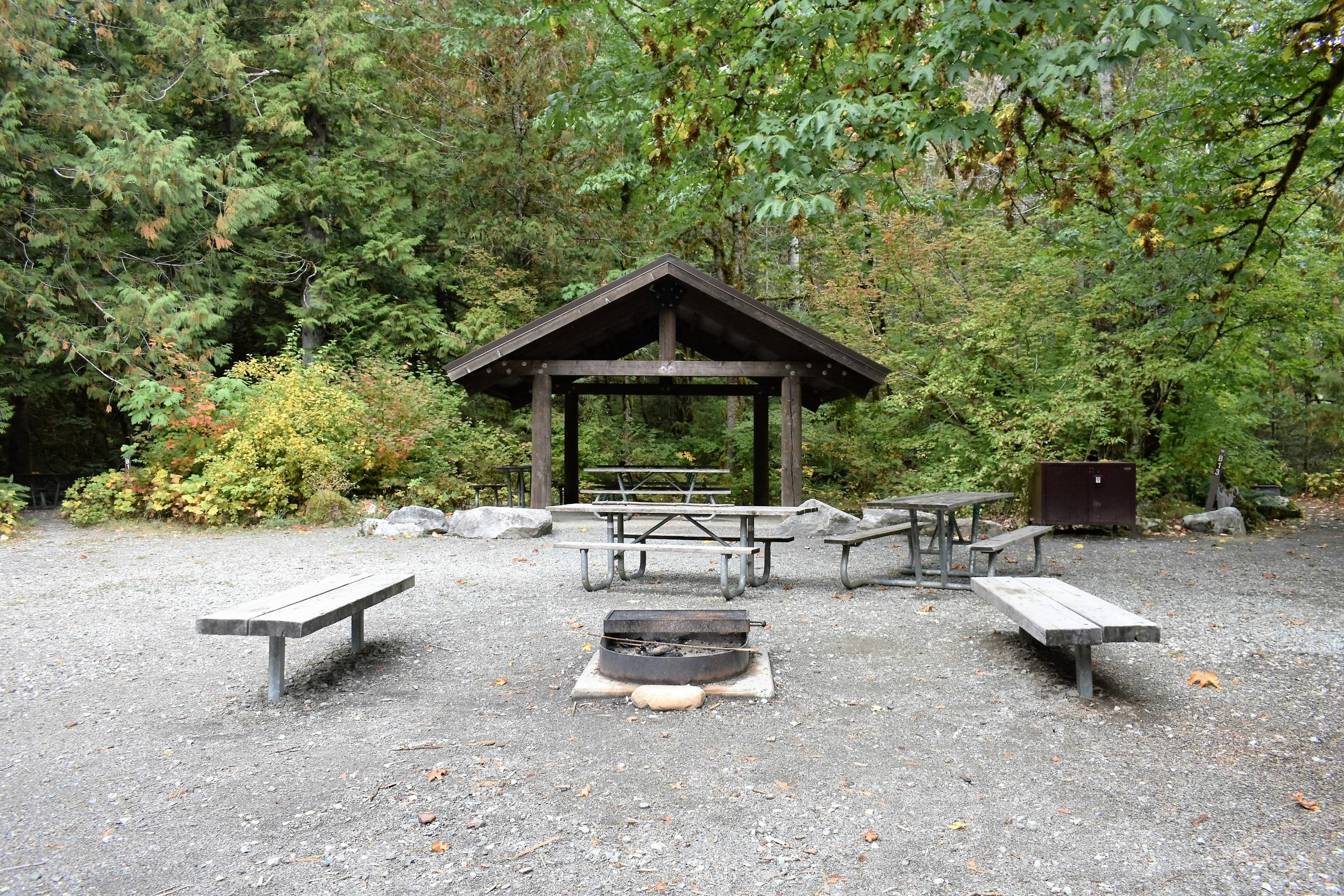 Shelter providing rain and sun protection for picnic tables with fire circle and benches in foregroundView of group shelter and campfire circle
