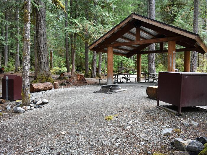 Shelter provided rain and sun protection to several picnic tables located underneath. Campfire ring and food storage lockers in foreground.View of shelter at Upper Goodell Group Campground