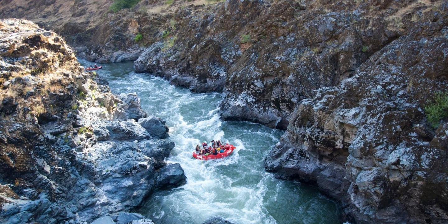A red raft floats through a rocky canyon on the Rogue Wild & Scenic River.