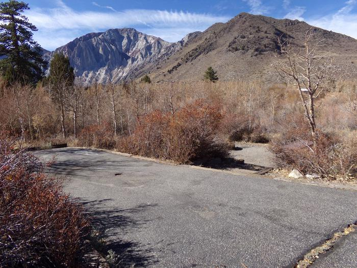 Convict Lake Campground site #27 featuring parking space, entrance to the wooded site, and mountain views.