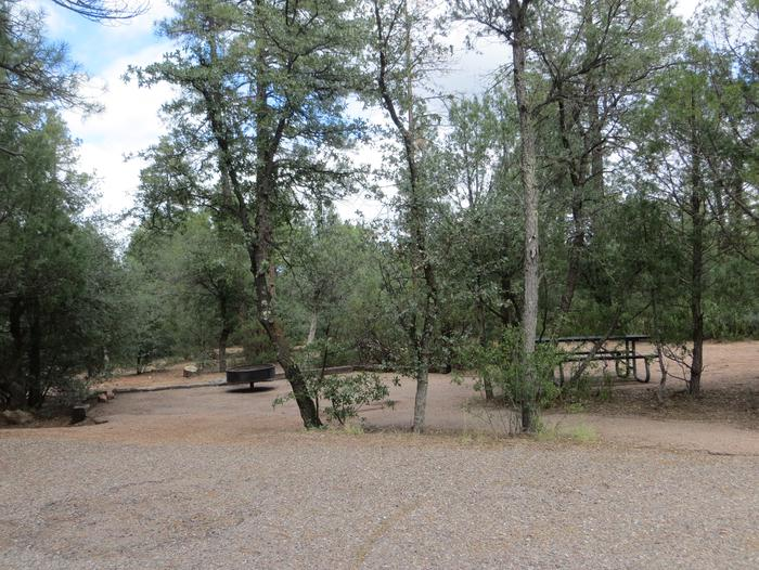 Houston Mesa, Elk Loop site #18 featuring entrance to the wooded site, fire pit, and picnic table.