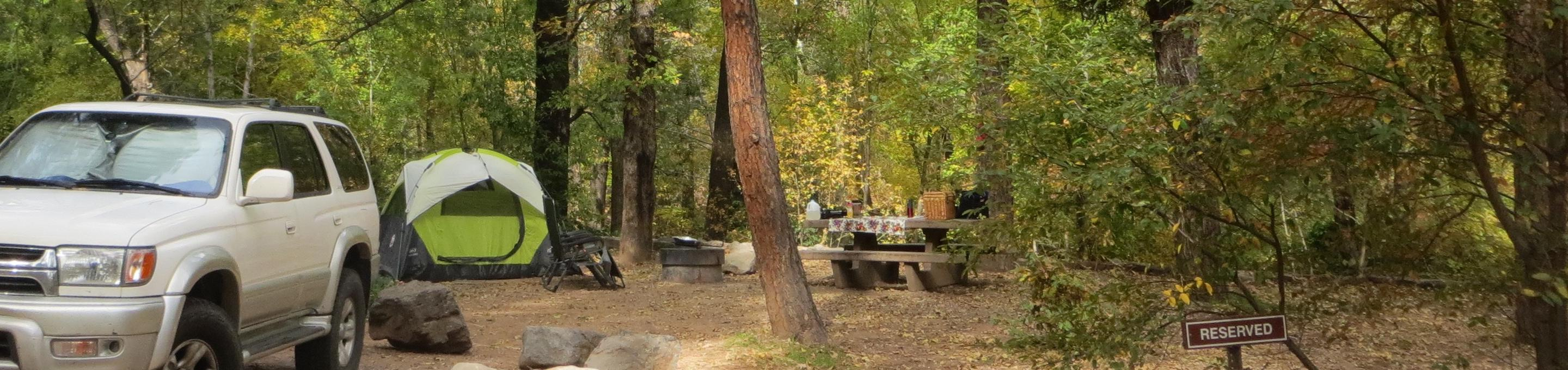 Manzanita Campground site #19 featuring the treed picnic area, camping space, and fire pit.