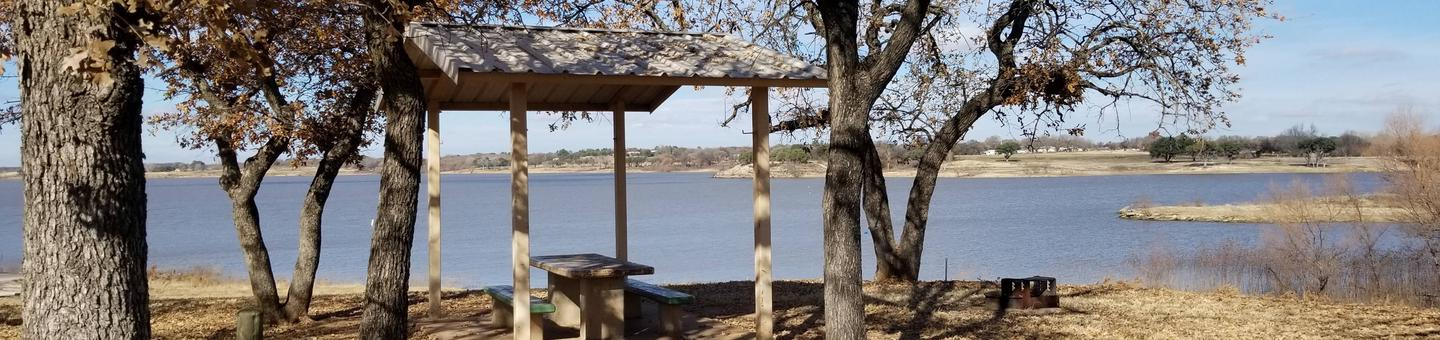Site 16View of Site 16, including covered picnic table, shade trees, and lake view