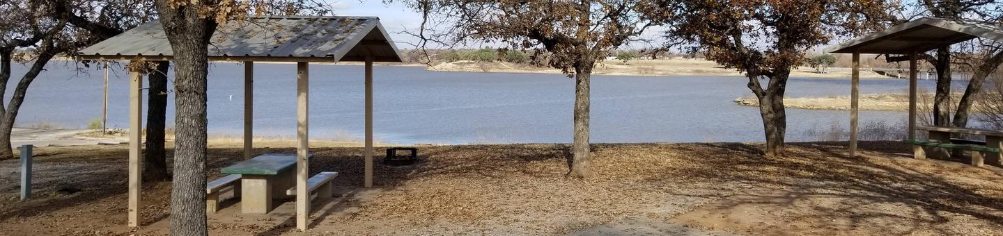 Site 17SView of Site 17S, including covered picnic table, shade trees, and lake view