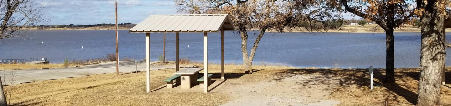 Site 18SView of Site 18S, including covered picnic table, shade trees, power hook-up, and lake view