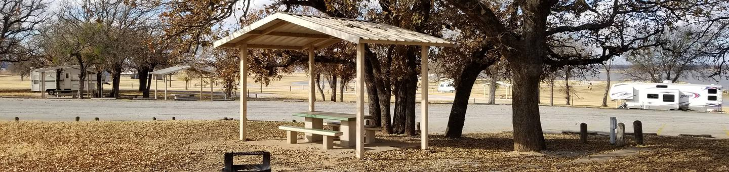 Site 20SView of Site 20S, including covered picnic table, shade trees, and lake view