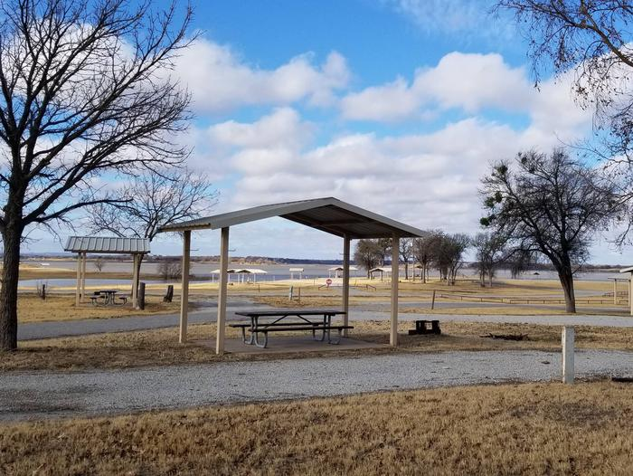Site 22SView of Site 22S, including covered picnic table, shade trees, and fire ring