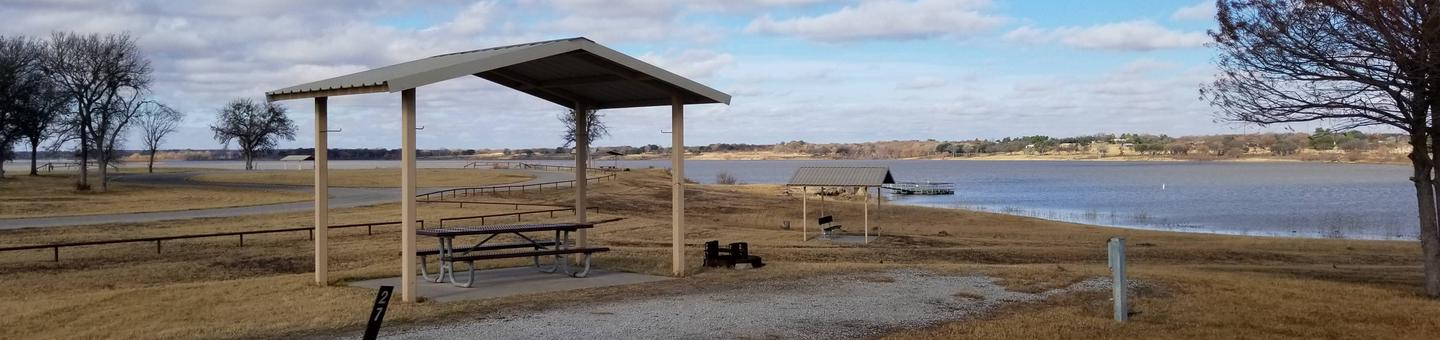 Site 27SView of Site 27S, including covered picnic table, shade trees, and lake view