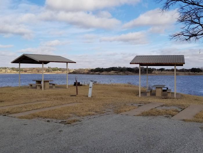 Site 31SDView of Site 31SD, including covered picnic tables, shade tree, and lake view