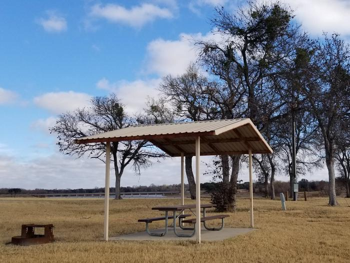 Site 39SDView of Site 39S, highlighting covered picnic table, shade trees, and fire ring.