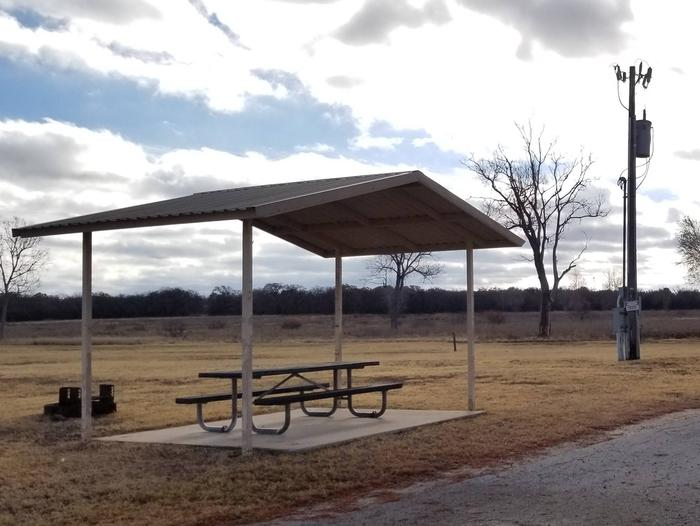 Site 48FView of Site 48F, highlighting covered picnic table, shade trees, and fire ring.