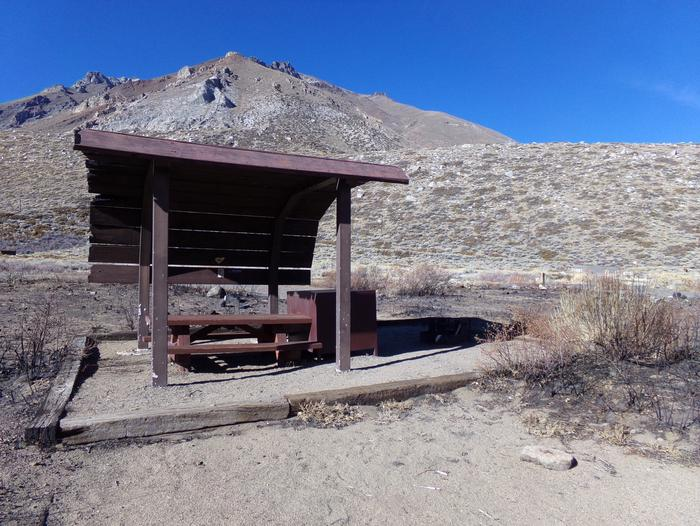McGee Creek Campground site #05 featuring shaded picnic area with fire pit and camping space.