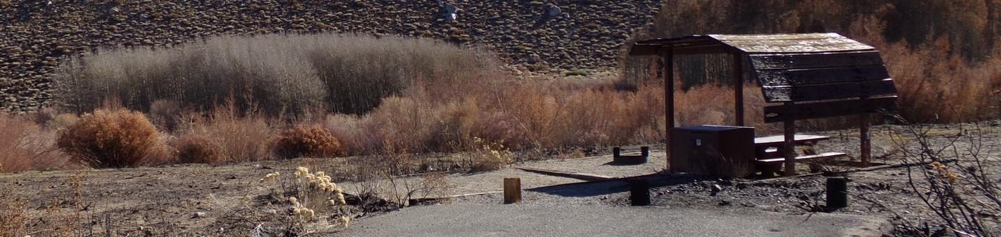 McGee Creek Campground site #06 featuring shaded picnic area with fire pit and camping space.