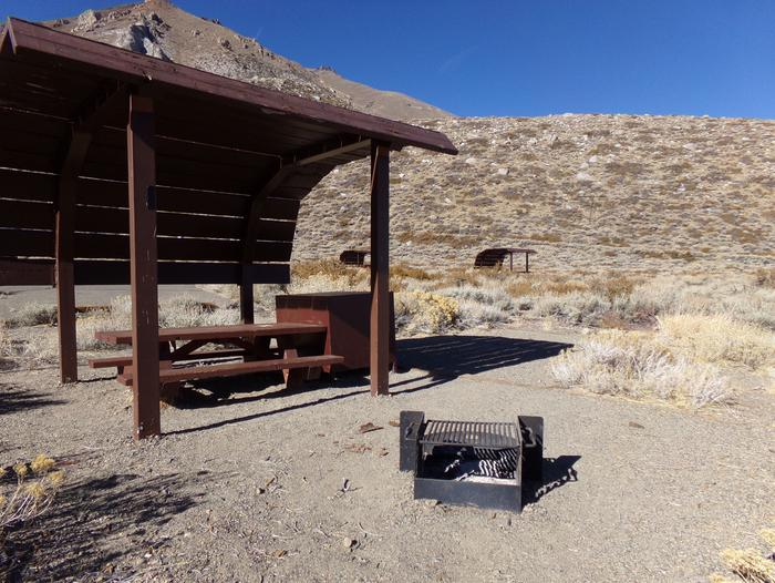 McGee Creek Campground site #11 featuring shaded picnic area with fire pit and camping space.