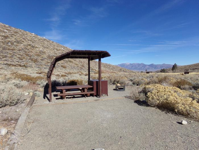 McGee Creek Campground site #12 featuring shaded picnic area with fire pit and camping space.