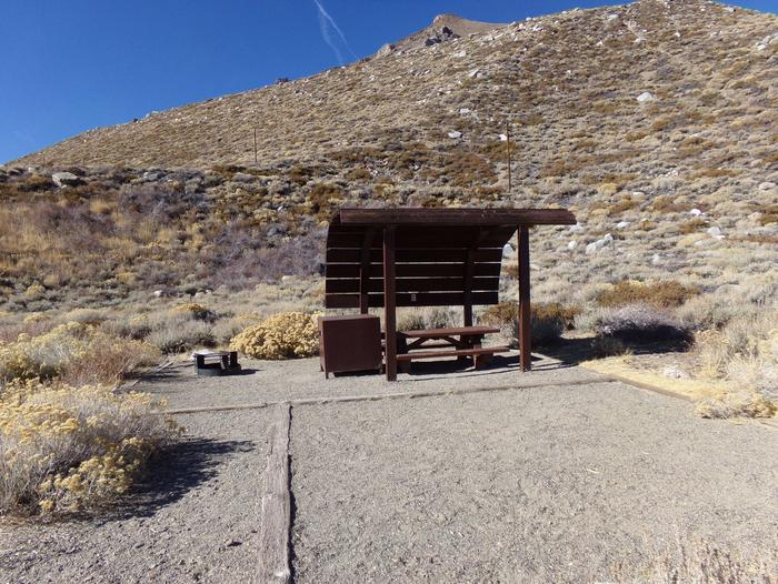 McGee Creek Campground site #15 featuring shaded picnic area with fire pit and camping space.