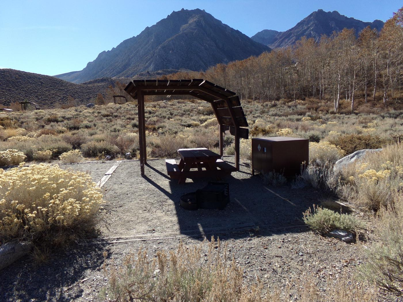 McGee Creek Campground site #16 featuring shaded picnic area with fire pit and camping space.