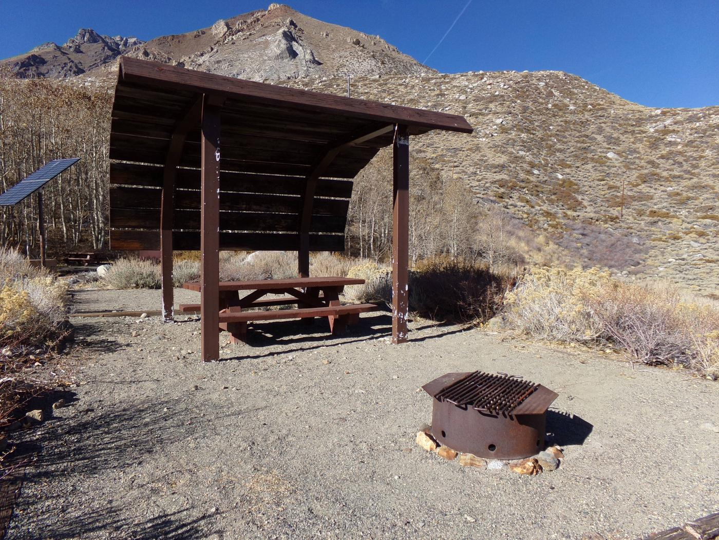 McGee Creek Campground site #21 featuring shaded picnic area with fire pit and camping space.