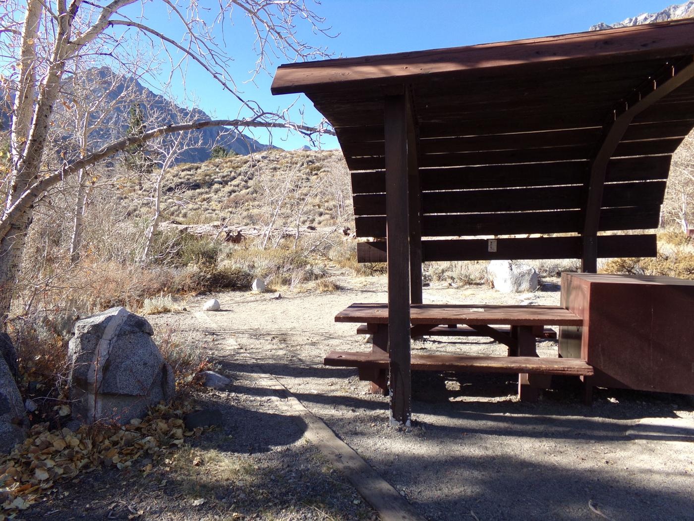 McGee Creek Campground site #26 featuring shaded picnic area with fire pit and camping space.