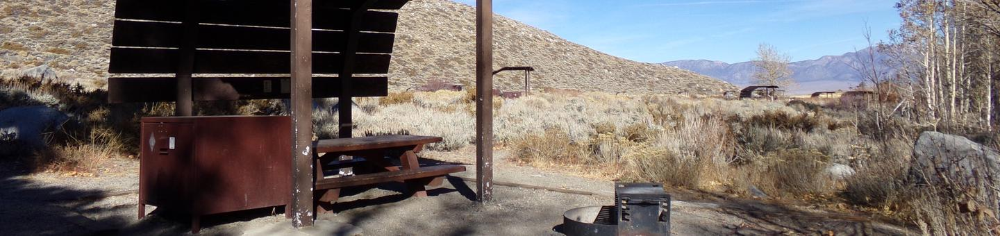 McGee Creek Campground site #27 featuring shaded picnic area with fire pit and camping space.