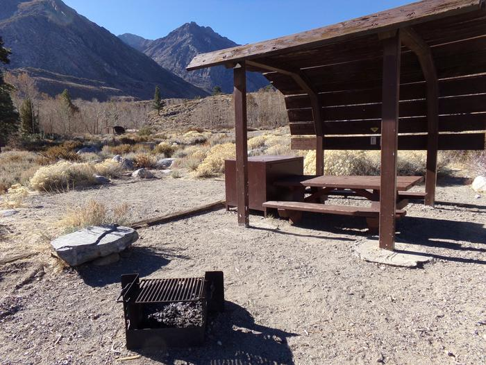 McGee Creek Campground site #28 featuring shaded picnic area with fire pit and camping space.