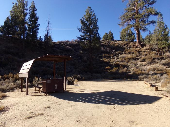 Tuff Campground site #15 featuring shaded picnic area with camping space and fire pit by the mountain side.