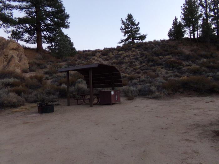 Tuff Campground site #16 featuring shaded picnic area with camping space and fire pit by the mountain side.