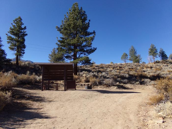 Tuff Campground site #23 featuring the shaded picnic area with camping space and fire pit by the mountain side.