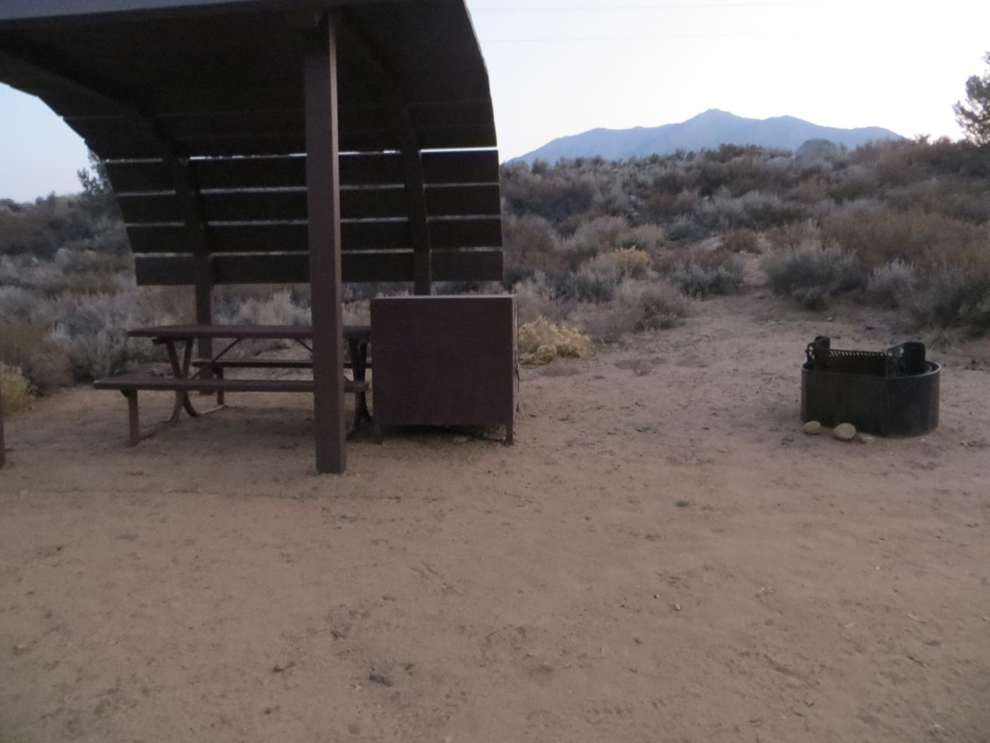 Tuff Campground site #24 featuring the shaded picnic area with camping space and fire pit by the mountain side.
